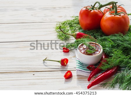 Tomato sauce salsa, hot chili, dill, fresh tomatoes and basil,  on wooden background.  ingredients. Top view