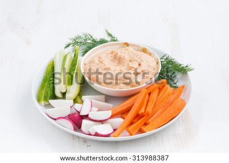 tomato sauce with tofu and fresh vegetables on white table, horizontal
