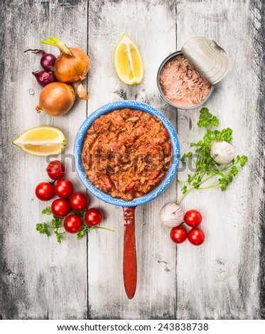 tomato sauce with tuna fish in old porridge pot and ingredient on white wooden background, top view - stock photo