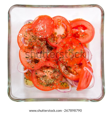 Tomato slices, onion with basil and olive oil in a glass bowl isolated on white background - stock photo