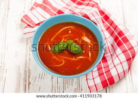 Tomato soup and basil on wooden table - stock photo