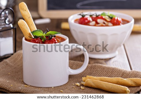 Tomato soup garnished with baked tomatoes and almond slices - stock photo