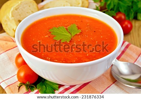 Tomato soup in a white bowl on a napkin, spoon, tomatoes, parsley, bread on a wooden boards background - stock photo