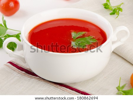 Tomato soup in a white bowl . Selective focus