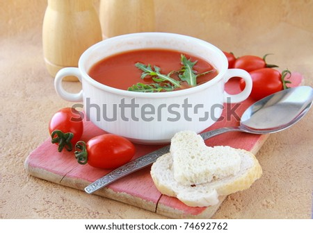 tomato soup in a white bowl with arugula and cherry tomatoes - stock photo