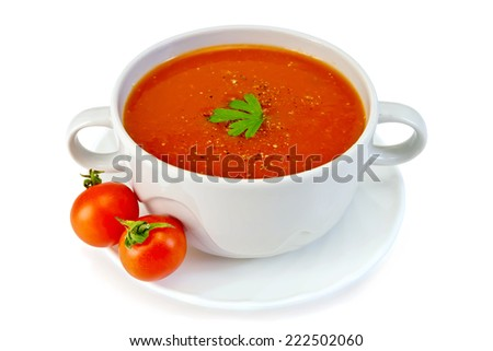 Tomato soup in a white bowl with parsley on a plate with tomatoes isolated on white background - stock photo
