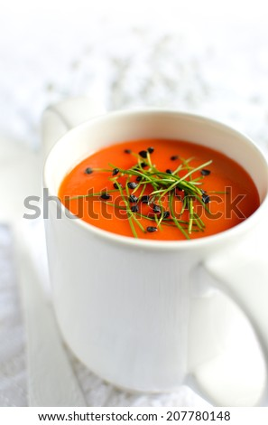 Tomato soup in a white mug with garlic chive garnish against a light background. Copy space. - stock photo