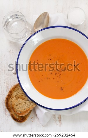 tomato soup in white plate with spoon and toast - stock photo