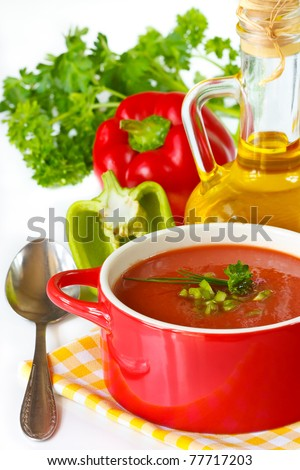 Tomato soup on a red ceramic saucepan and vegetables. - stock photo
