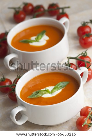 Tomato soup topped with cream and basil in a bowl