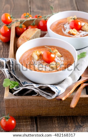 Tomato soup with cream and croutons and parsley leaves in a white bowl on a napkin on a wooden table vertical view