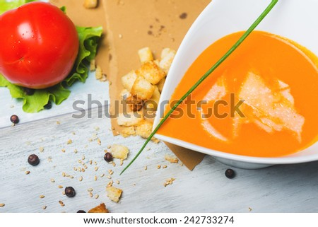 Tomato soup with croutons and shredded cheese on the wooden table  - stock photo