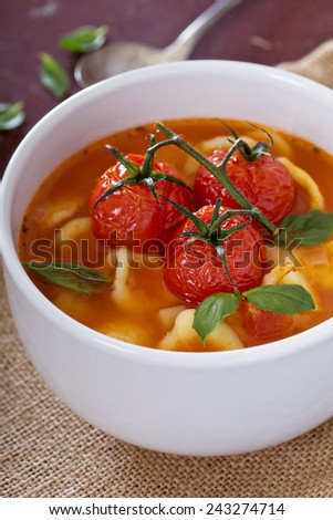 Tomato soup with pasta garnished with baked tomatoes - stock photo