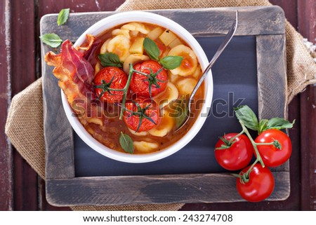 Tomato soup with pasta garnished with tomatoes and bacon - stock photo