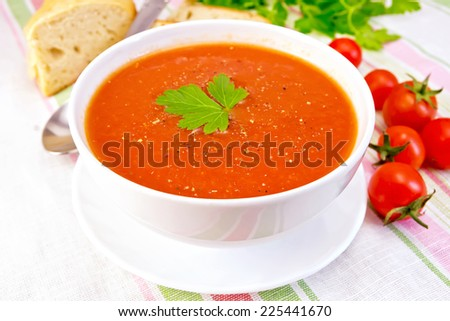 Tomato soup with peppers in white bowl on a saucer, tomatoes, bread, parsley on a linen tablecloth background - stock photo