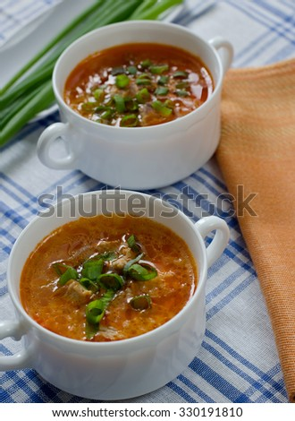 Tomato soup with rice and meat dusted with chopped green onions.
