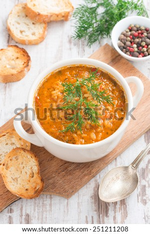 tomato soup with rice and vegetables in a white saucepan and bread, vertical, top view, close-up - stock photo