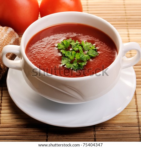 tomato soup with tomatoes in background - stock photo