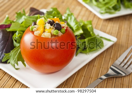 Tomato stuffed with quinoa and vegetables with field greens salad - stock photo