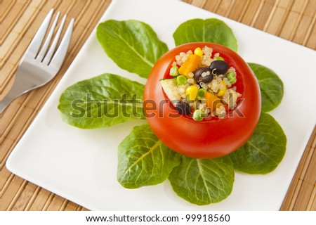 Tomato stuffed with quinoa, black beans and vegetables with greens on a white plate - stock photo