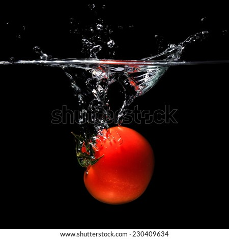Tomato thrown into water on black background.