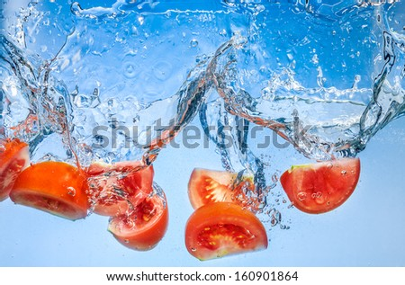 Tomato. Vegetables fall deeply under water with a big splash - stock photo
