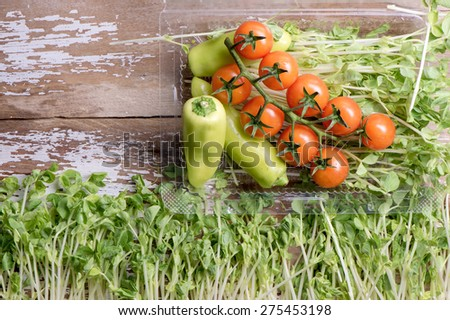 Tomato wit Pea sprout on wood top. - stock photo
