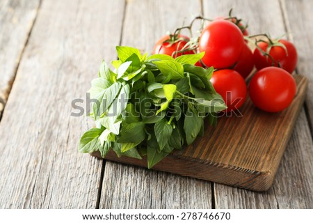Tomatoes and basil leaves on grey wooden background - stock photo