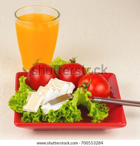 Tomatoes and cheese slices lie on a sheet of fresh salad in a red plate. A glass of orange juice stands side by side on the table.