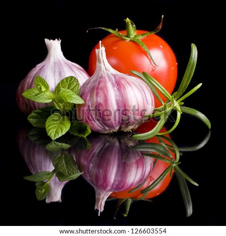Tomatoes and garlic in wooden plate on black background. - stock photo