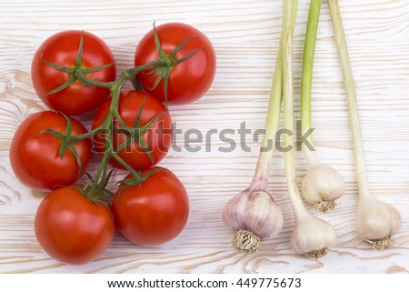 tomatoes and garlic on old wooden table.