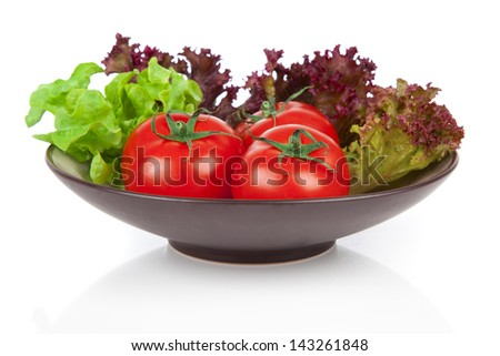 tomatoes and green salad in the bowl, over white background