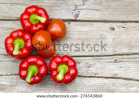 tomatoes and peppers on wooden background - stock photo