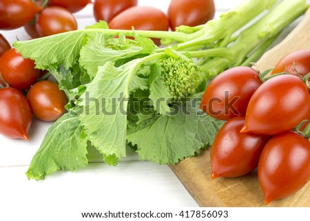 Tomatoes and turnips on wooden background