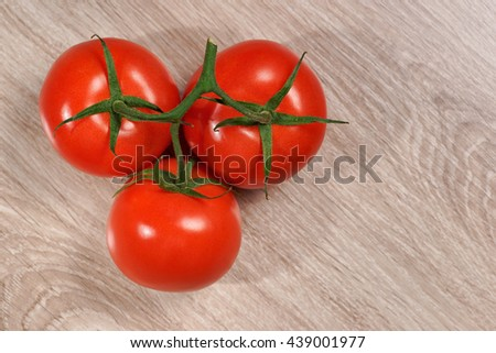 Tomatoes, bunch of vegetables on a wooden table, view from above