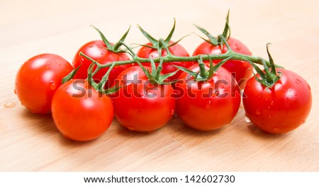 Tomatoes cherry branch on a wooden board