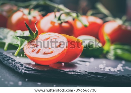 Tomatoes. Cherry tomatoes. Cocktail tomatoes. Fresh grape tomatoes carafe with olive oil on table. Toned photo - stock photo