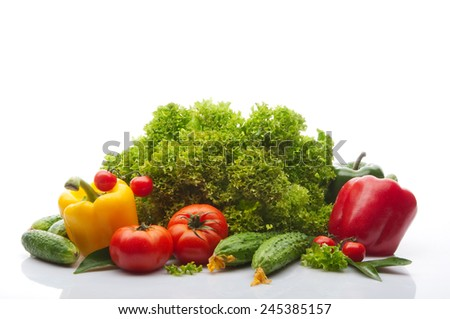 Tomatoes, cherry tomatoes, cucumbers, salad, yellow red and green pepper on white background