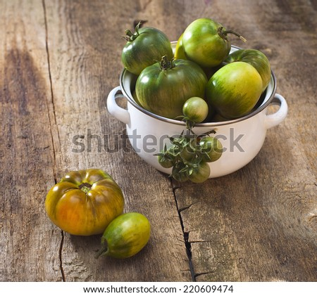 Tomatoes, cooked with herbs for the preservation on the old wooden table. - stock photo