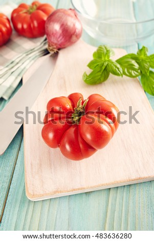 Tomatoes corleone type for sauce on a aqua wooden table with basil and onion