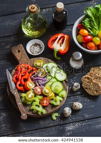 Tomatoes, cucumber, celery, bell pepper, red onion, quail eggs,olive oil, balsamic vinegar, garden herbs and spices - Ingredients to prepare vegetable salad, on a rustic wooden board. Healthy food - stock photo