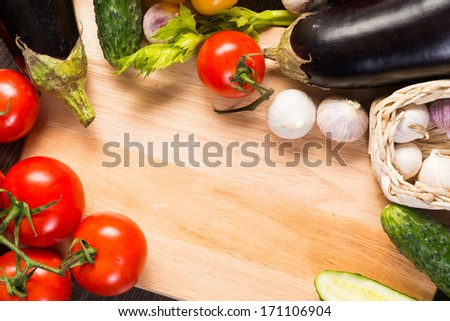 tomatoes, cucumber, garlic, fresh herbs on chopping board