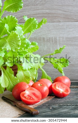 Tomatoes, fresh lettuce on a wooden table. Rustic style - stock photo