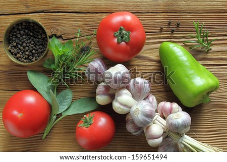 Tomatoes, garlic and fresh herbs on wooden background.