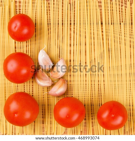 Tomatoes, garlic and spaghetti on the wooden background