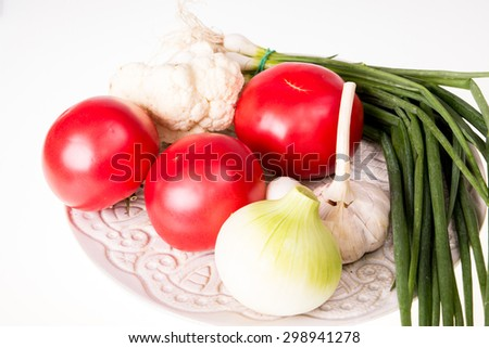 Tomatoes, garlic, onion and chive on plate isolated