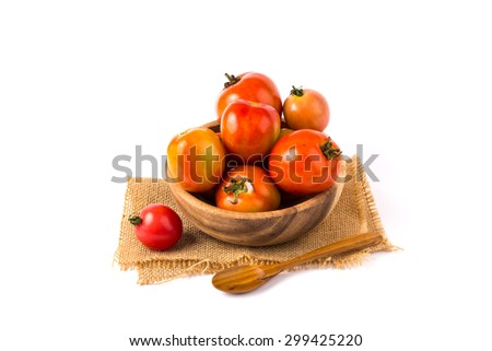 Tomatoes in a wooden bowl on a white background.