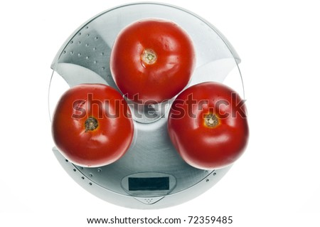 Tomatoes isolated on food scale - stock photo