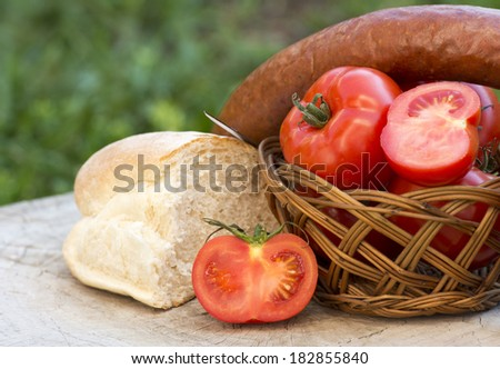Tomatoes , ketchup , bread and sausage on old wooden table