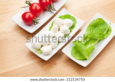 Tomatoes, mozzarella and green salad leaves on wooden table background - stock photo